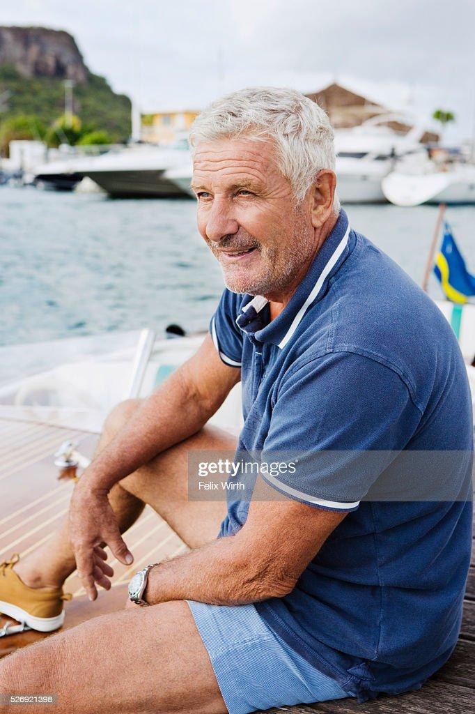 Senior man sitting on jetty : Stock-Foto