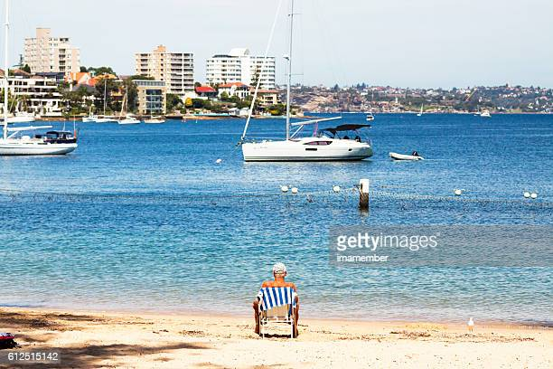 Senior man sitting on Manly beach after swim, copy space