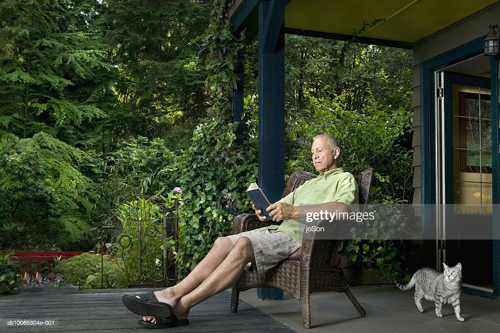 Senior man sitting on porch reading book, cat passing by : Foto stock