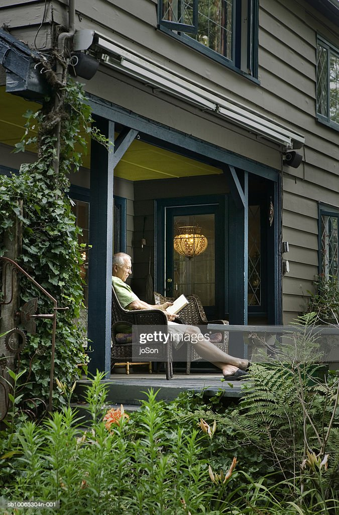 Senior man sitting on porch reading book : Foto stock