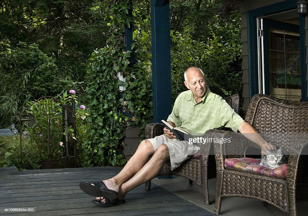 Senior man sitting on porch with book, petting cat : Foto stock