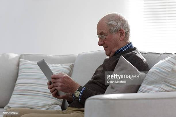 Senior man sitting on sofa using digital tablet