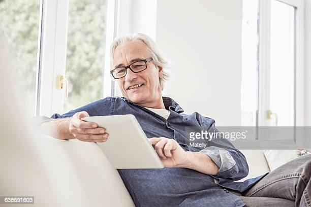 senior man sitting on sofa, using digital tablet - one senior man only stock pictures, royalty-free photos & images