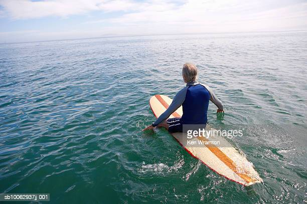 Senior man sitting on surfboard at sea, rear view