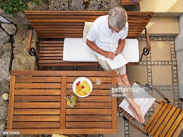 Senior man sitting on terrace reading book
