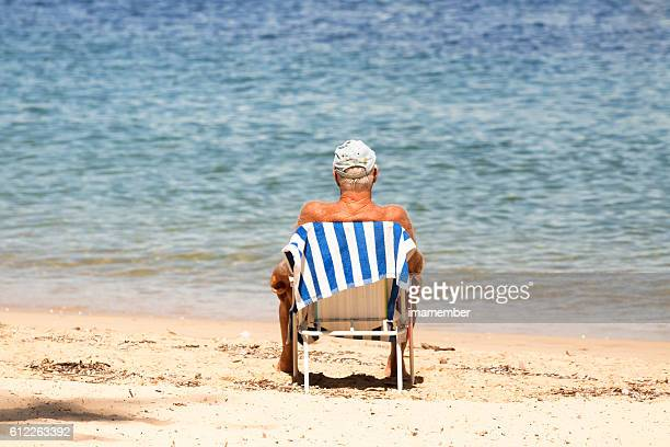 Senior man sitting on the beach after swim, copy space