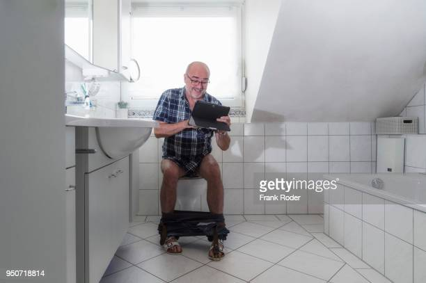 senior man sitting on the toilet, laughing whilst surfing the internet on a tablet, germany - human toilet stock-fotos und bilder