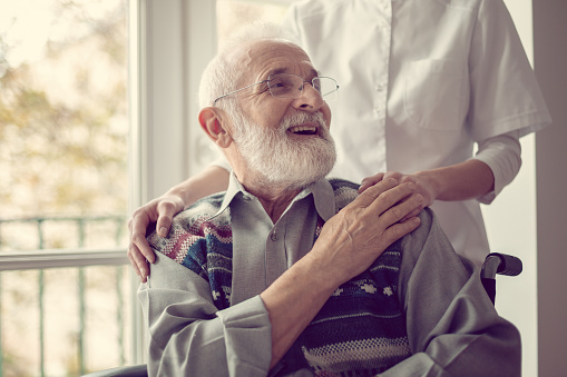 Senior man sitting on the wheelchair, laughing and holding his nurse's hand 1165922756