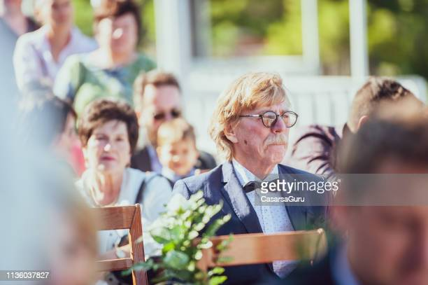 senior man sitting on wedding ceremony - wedding ceremony stock pictures, royalty-free photos & images
