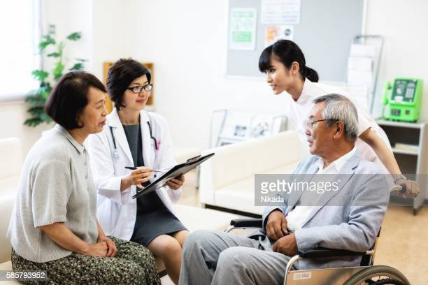 senior man sitting on wheelchair and talking with  with doctor