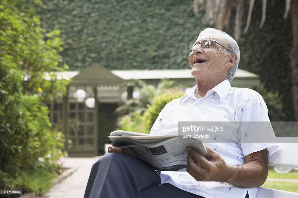 Senior man sitting outdoors with newspaper laughing : Stock Photo