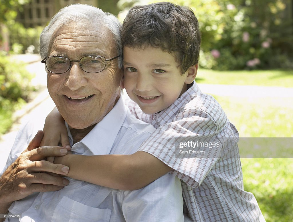 Senior man sitting outdoors with young boy being affectionate toward him and smiling : Stock Photo