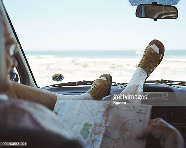 Senior man sitting with feet up on campervan dashboard, close-up