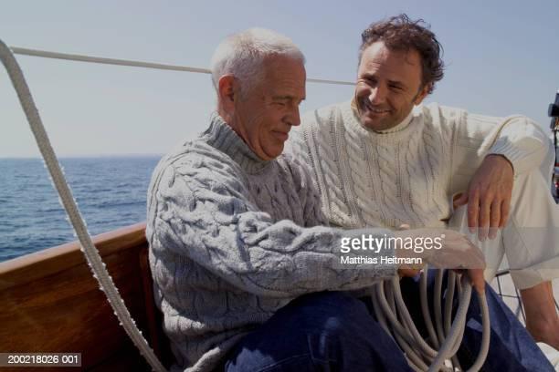 Senior man sitting with mature man on yacht, looping rope, smiling