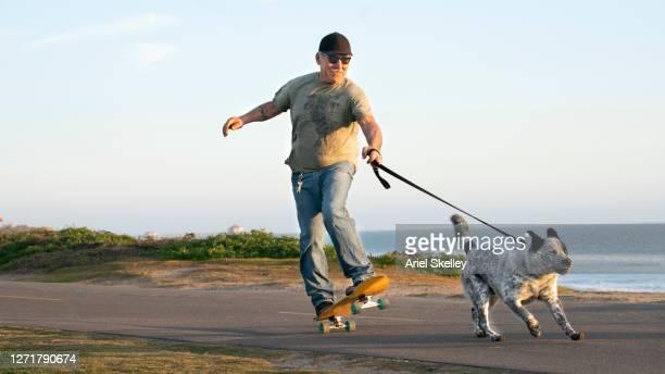 senior man skateboarding with his dog - 気が若い ストックフォトと画像