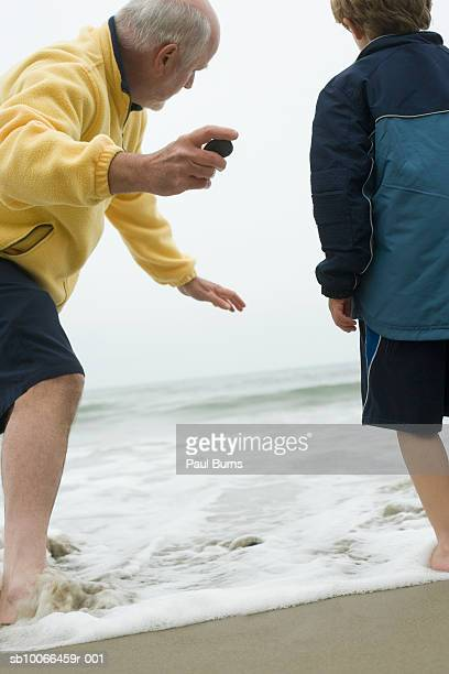 Senior man skimming rocks with grandson (8-9) on beach, rear view