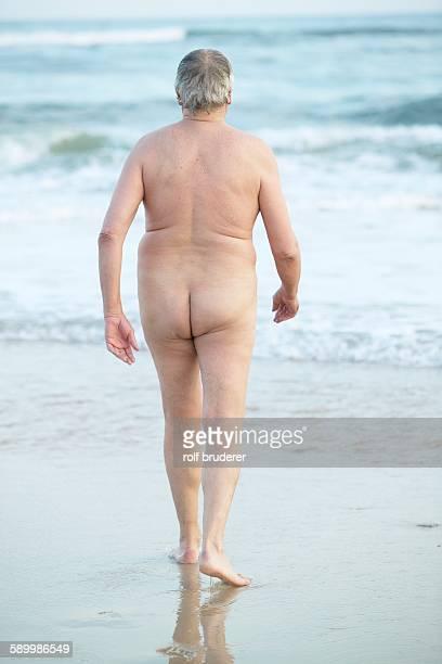 senior man skinny dipping - senioren aktfotos stock-fotos und bilder