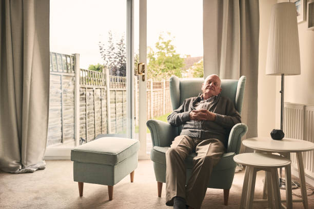 senior man sleeping on a armchair - old man napping stock pictures, royalty-free photos & images