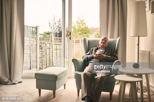 senior man sleeping on a armchair - armchair stock pictures, royalty-free photos & images