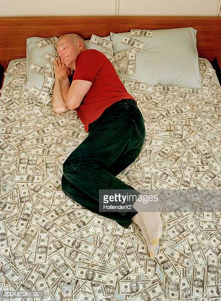 Senior man sleeping on bed covered with US banknotes, elevated view