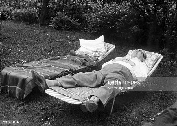 A senior man sleeps in a lawn chair while his partner is away