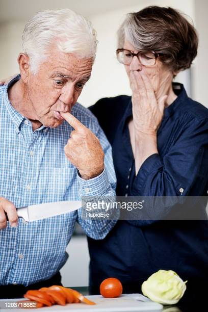senior man slicing vegetables cuts himself, wife looks shocked - compassionate eye stock pictures, royalty-free photos & images