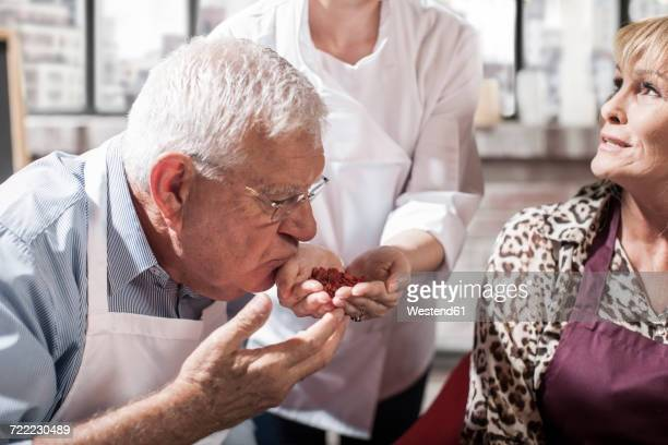 Senior man smelling seeds from chefs hand in cooking class