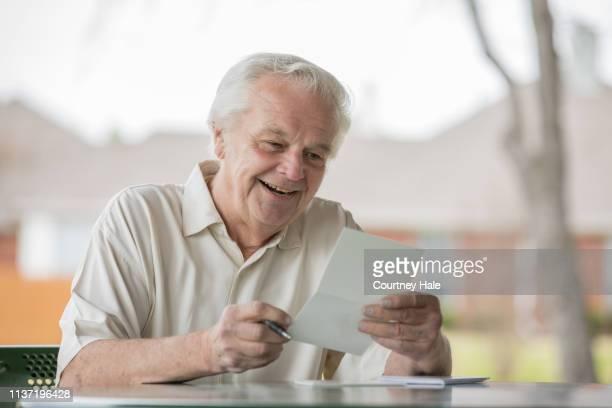 senior man smiles while reading a letter or greeting card outdoors - responder imagens e fotografias de stock