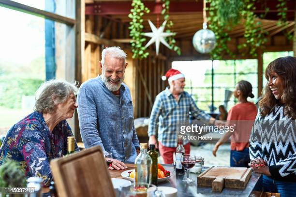 senior man smiling and laughing with friends at christmas gathering - country christmas stock pictures, royalty-free photos & images