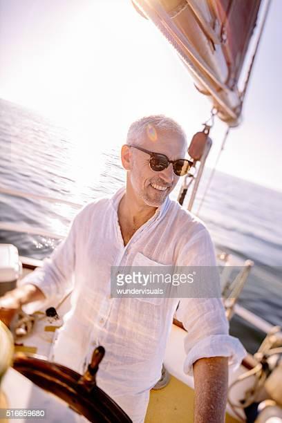 Homme Senior souriant en tant que capitaine de bateau sur son bateau de plaisance
