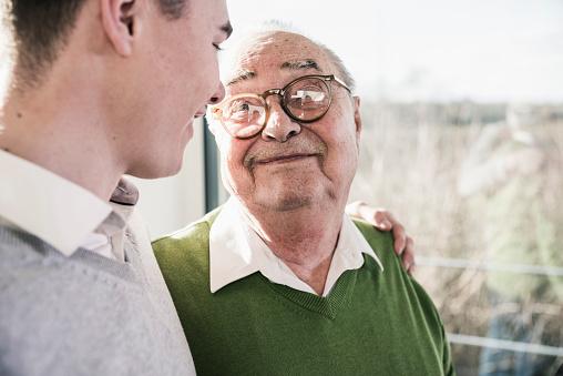 Senior man smiling at young man - gettyimageskorea