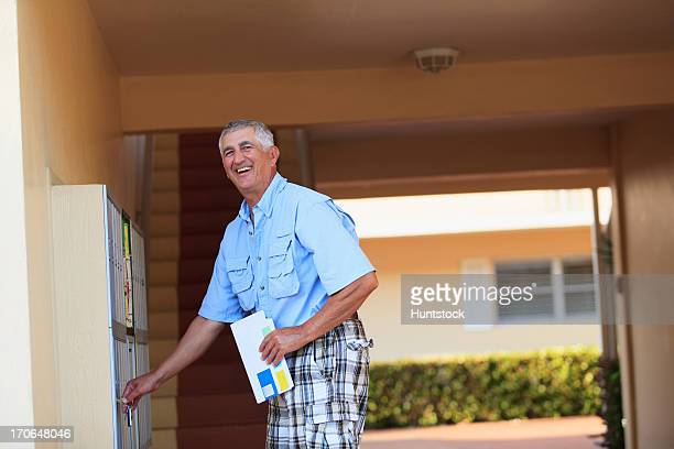 senior man smiling checking his mailbox - domestic mailbox stock pictures, royalty-free photos & images