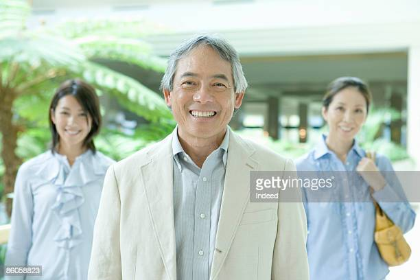 Senior man smiling, daughter and wife in behind