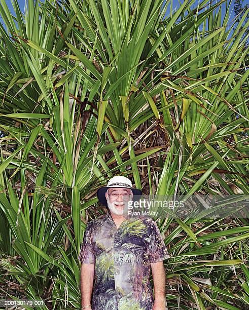Homme Senior souriant devant les feuilles verdoyantes des palmiers, portrait