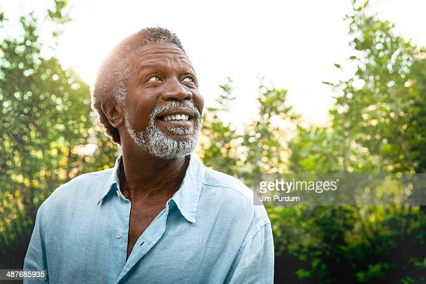 senior man smiling outdoors - speranza foto e immagini stock