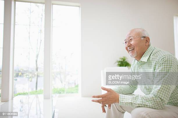 Senior man smiling, sitting on couch