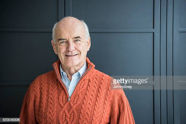 Senior man smiling, wearing orange sweater