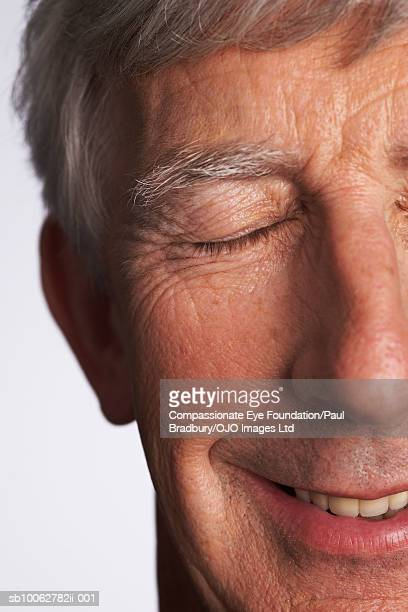"""senior man smiling with eyes shut, close-up of face - """"compassionate eye"""" stock pictures, royalty-free photos & images"""