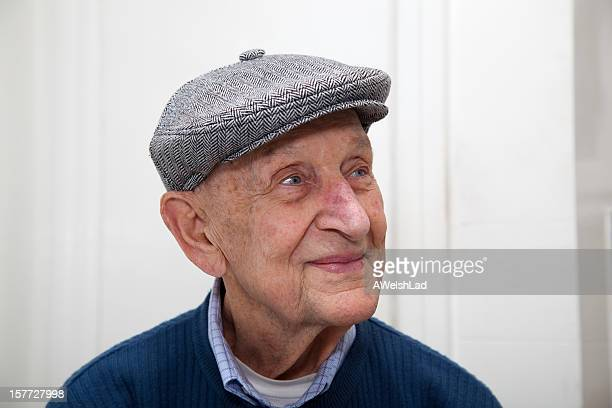 Senior man smiling with grey herringbone flat cap