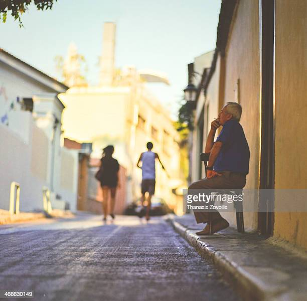CONTENT] Senior man smoking a cigarette while tourist passing by in Plaka Athens Greece