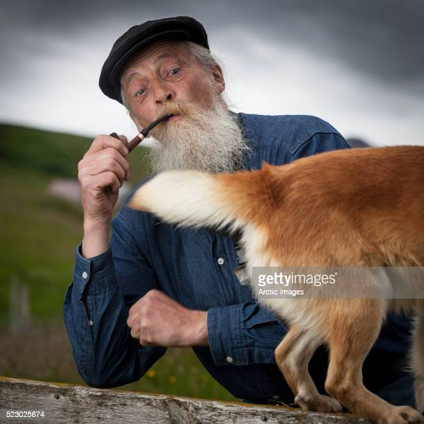 Senior man smoking a pipe with dog