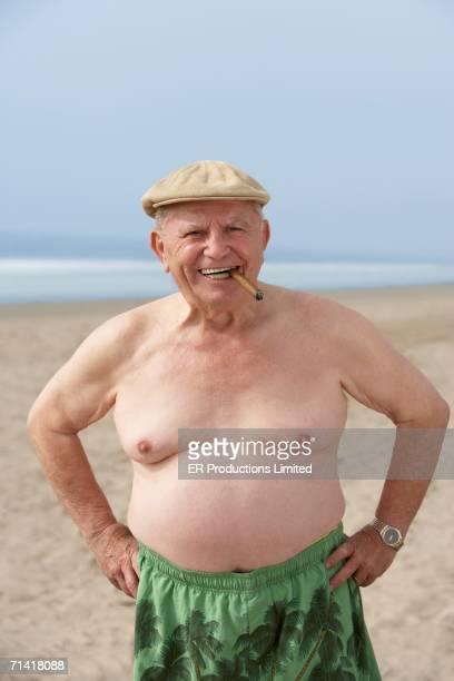 senior man smoking cigar at the beach - sin camisa fotografías e imágenes de stock