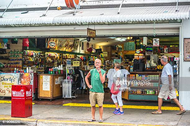 senior man smoking cigar on duval street, key west - duval street stock pictures, royalty-free photos & images