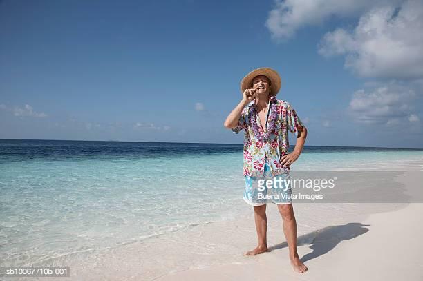 Senior man smoking on beach, portrait