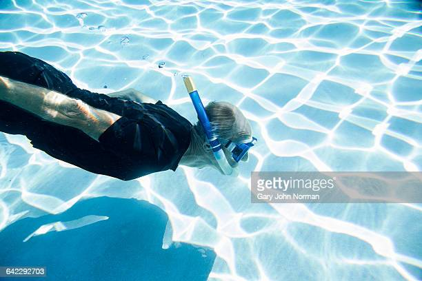 senior man snorkeling in swimming pool - norman elder stock photos and pictures