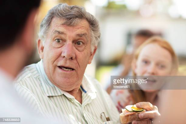 Senior man socializing on a garden party