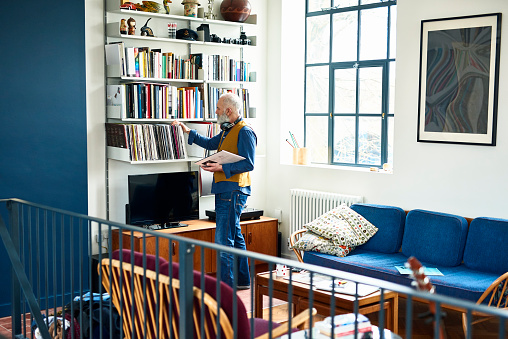 Senior man sorting through his record collection in living room - gettyimageskorea
