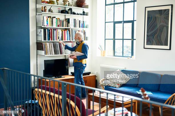 senior man sorting through his record collection in living room - arrangement stock pictures, royalty-free photos & images
