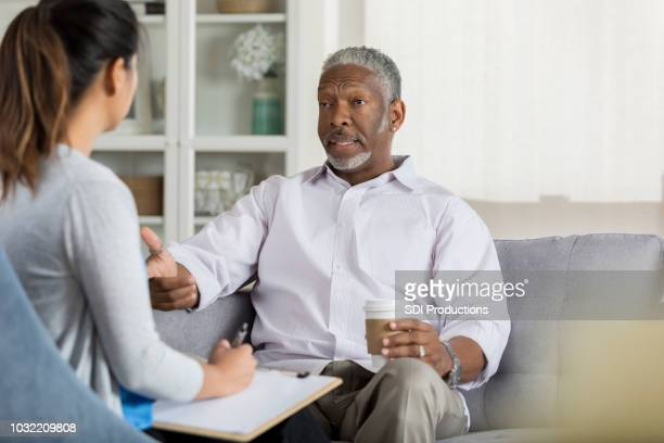 senior man speaks openly with attentive therapist - psychologist stock photos and pictures