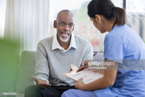 senior man speaks with home health nurse - visita imagens e fotografias de stock
